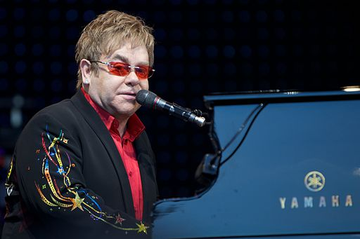 Elton John playing the piano and singing in a mic